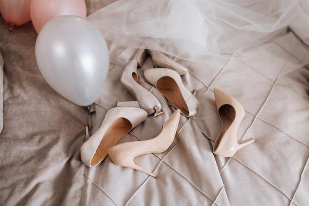 Zapatos beige están acostados sobre la manta cerca del velo y globos