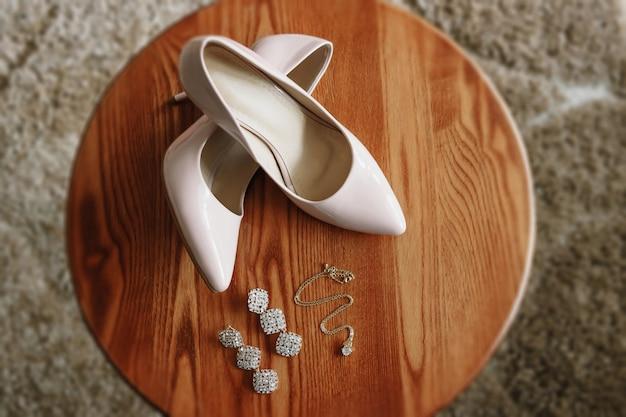 Zapatos biege de novia en el talón sobre una alfombra.
