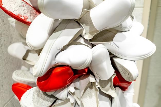 Zapatos blancos y rojos colgaban del escaparate.