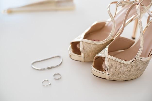 Zapatos de boda nupciales y joyas de acento, pendientes y pulsera.