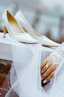 Los zapatos de boda con tacones cuelgan de una cerca blanca antes de que la novia se los ponga para la ceremonia de boda.