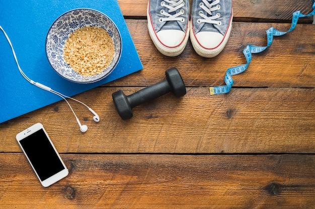Zapatos; cinta métrica; pesa; auricular; teléfono celular y tazón de avena en mesa de madera con textura