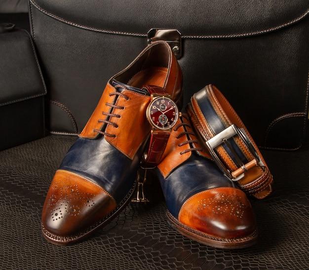 Zapatos de cuero y accesorios para hombres sobre fondo negro
