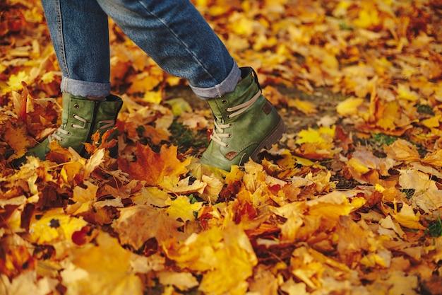 Zapatos de cuero caminando sobre hojas de otoño al aire libre