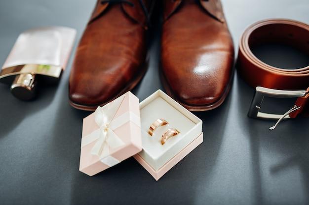 Zapatos de cuero marrón, cinturón, perfume y anillos dorados.