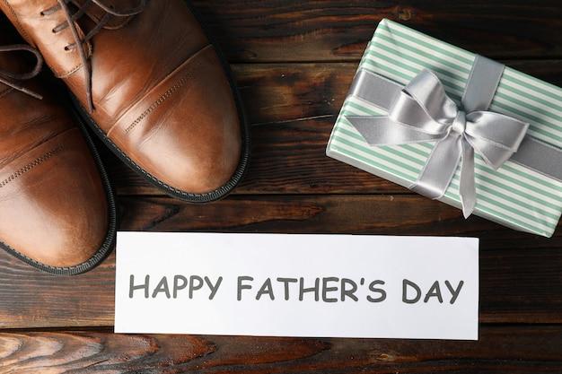 Zapatos de cuero marrón, inscripción feliz día del padre y caja de regalo sobre fondo de madera