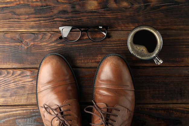 Zapatos de cuero marrón, taza de café y vasos sobre fondo de madera