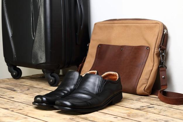 Zapatos de cuero negro y bolsa de viaje de equipaje en la mesa de madera