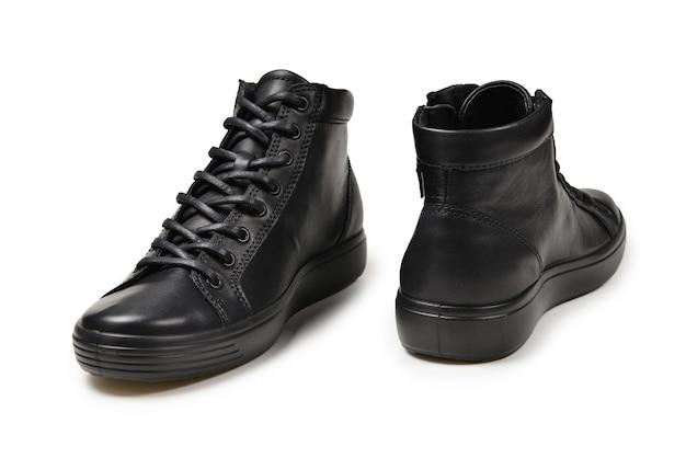Zapatos de cuero negro para hombre y una cámara negra sobre un fondo blanco aislado