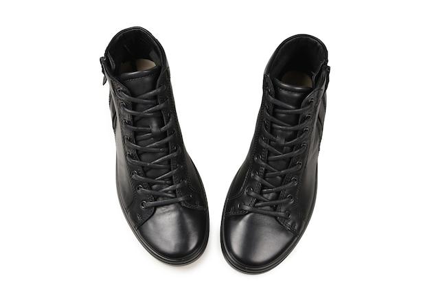 Zapatos de cuero negro para hombres y una cámara negra sobre un fondo blanco aislado. copie el espacio.