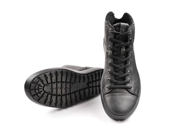 Zapatos de cuero negros de en y una cámara negra sobre fondo negro. copie el espacio.