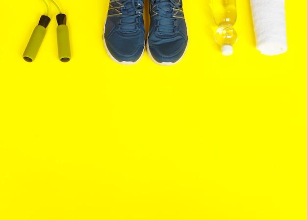 Zapatos del deporte, cuerda que salta, manzana y botella de agua en fondo amarillo.