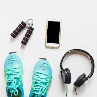 Zapatos deportivos color turquesa; auricular; teléfono móvil y agarre de la mano sobre fondo blanco