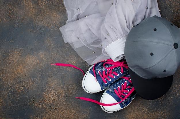 Zapatos deportivos, falda de gasa y gorra de béisbol en el suelo.