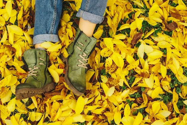 Zapatos en hojas amarillas de otoño