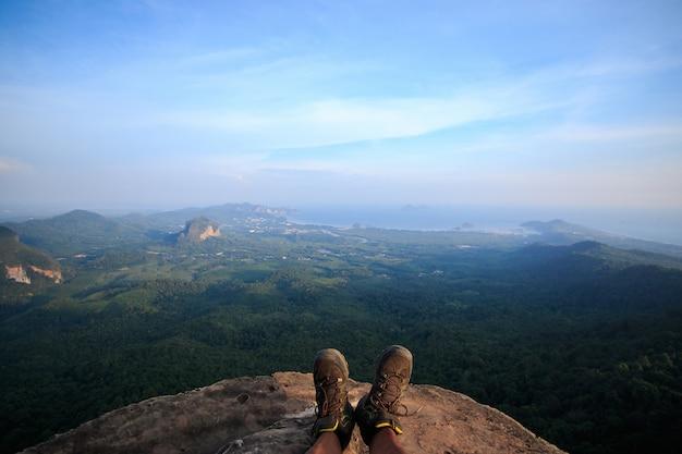 Zapatos de hombre en el acantilado hay una vista debajo del bosque.