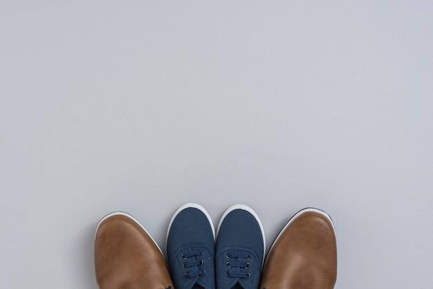 Zapatos de hombre y niños en mesa gris.