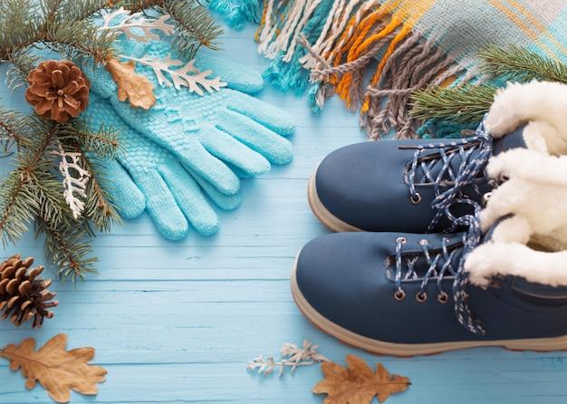 Zapatos de invierno azul y guantes en madera azul