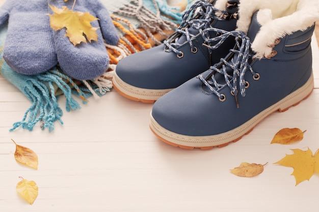 Zapatos de invierno azul y guantes sobre fondo blanco de madera