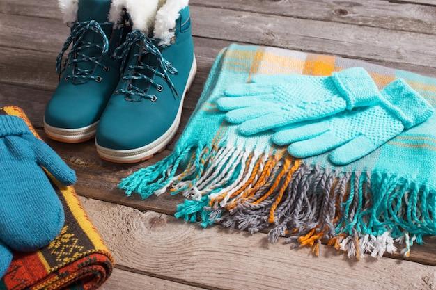 Zapatos de invierno, guantes, bufandas sobre fondo de madera vieja