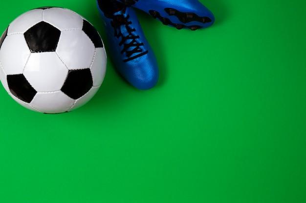 Zapatos de jugador de fútbol soccer con balón de fútbol sobre fondo verde