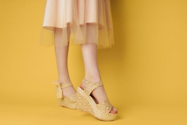 Zapatos de mujer beige fondo amarillo posando moda