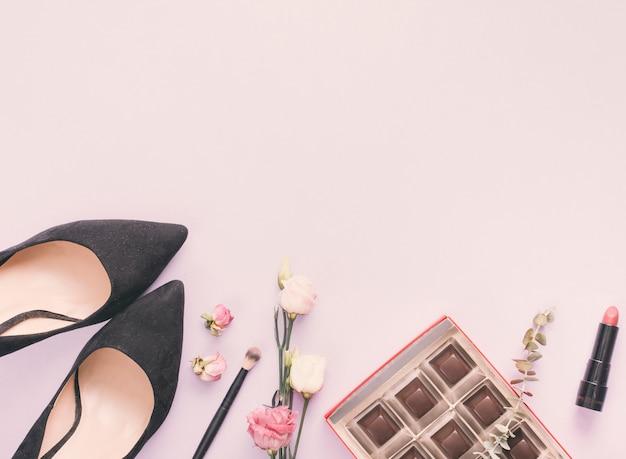 Zapatos de mujer con cosmeticos y rosas en mesa.