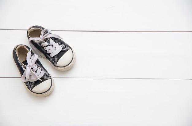 Zapatos negros para niños sobre suelo de madera.