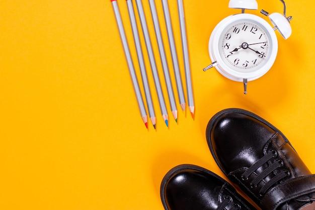 Zapatos negros, reloj despertador y lápices.