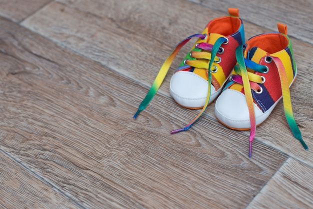 Zapatos para niños de colores sobre el piso de madera