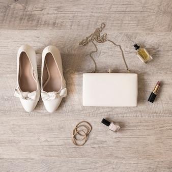 Zapatos de novia blancos; perfume; lápiz labial; cintas para el pelo; clutch y cintas para el pelo sobre fondo de madera.