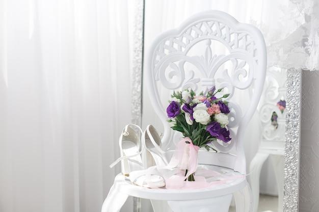 Zapatos de novia en una silla blanca con espacio para copiar texto