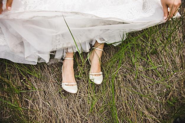 Zapatos nupciales en su boda con los pies de la novia