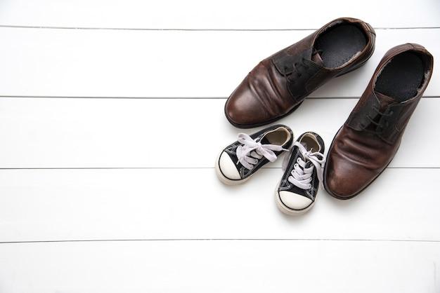 Los zapatos de padre e hijo en el fondo blanco de madera - concepto cuidar