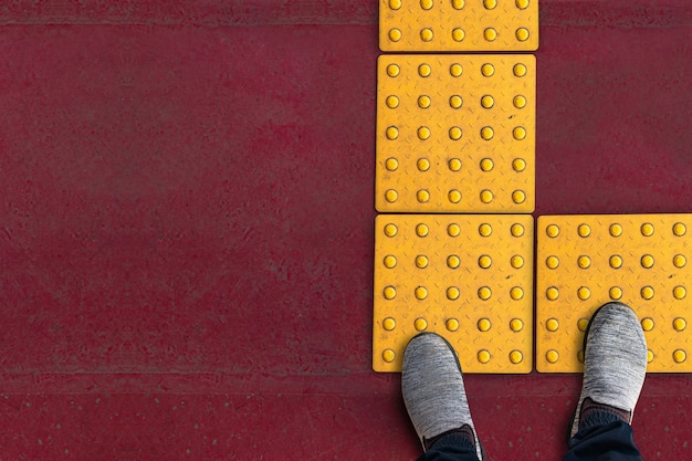 Zapatos en pavimento táctil de punto amarillo áspero para discapacitados ciegos en el camino de baldosas en japón, pasarela para personas con ceguera.