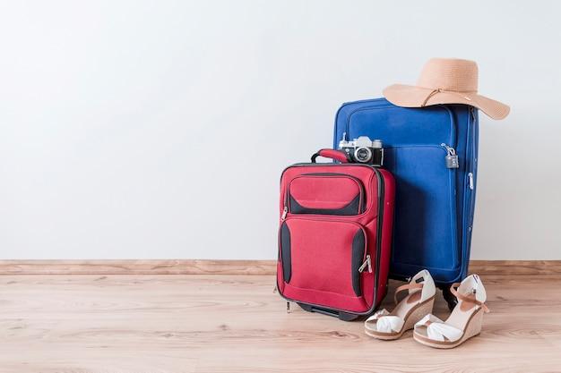 Zapatos peep-toe y sombrero cerca de maletas y cámara