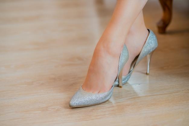Zapatos plateados con tacones altos. pies en zapatos de mujer de plata de lujo. zapatillas elegantes.