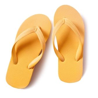 Los zapatos de la playa de la chancleta amarillean aislado en el fondo blanco