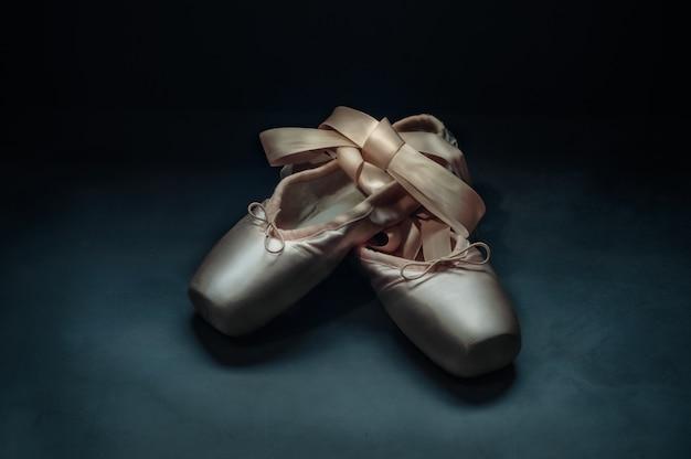 Los zapatos pointe de ballet con un lazo de cintas bellamente doblado sobre un fondo oscuro.