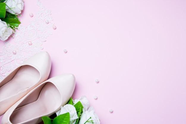 Zapatos y ramo de la boda que mienten en fondo rosado. de cerca. tendido plano vista superior.