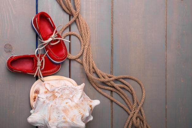 Zapatos rojos del barco cerca de la cáscara grande y cuerda en madera.