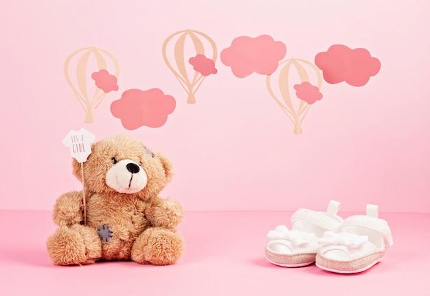 Zapatos rosados lindos de la niña sobre el fondo en colores pastel rosado con las nubes y los globos