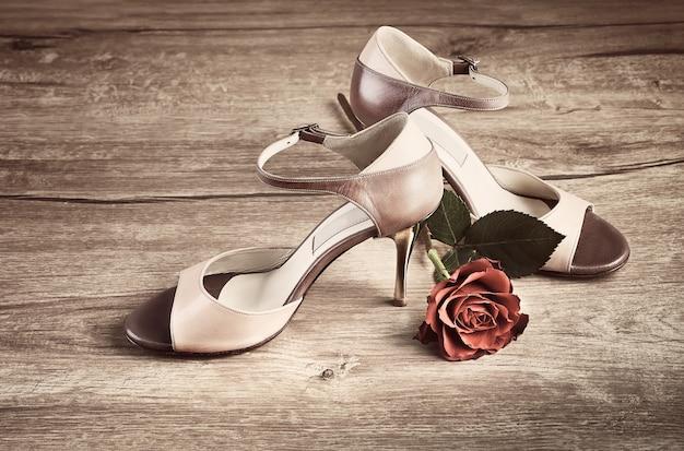 Zapatos de tango argentino con una rosa sobre madera