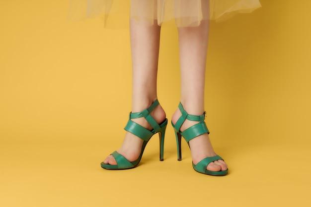 Zapatos verdes en piernas femeninas posando closeup fondo amarillo