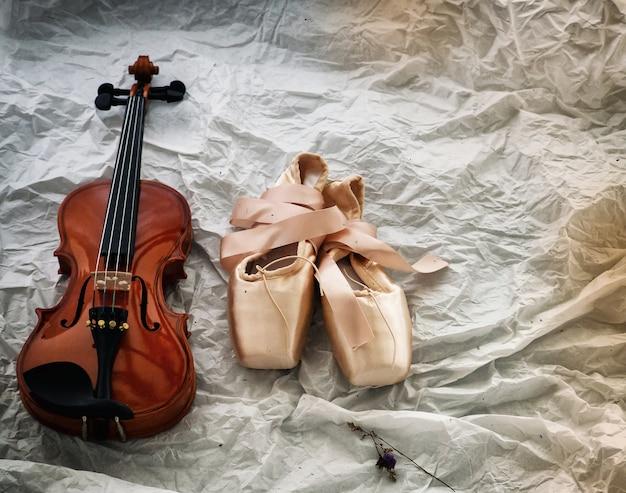 Zapatos de violín y ballet puestos en estilo de fondo, vintage y arte