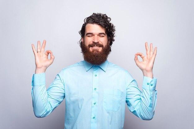 Zen. foto de hombre barbudo con camisa azul haciendo gesto zen.
