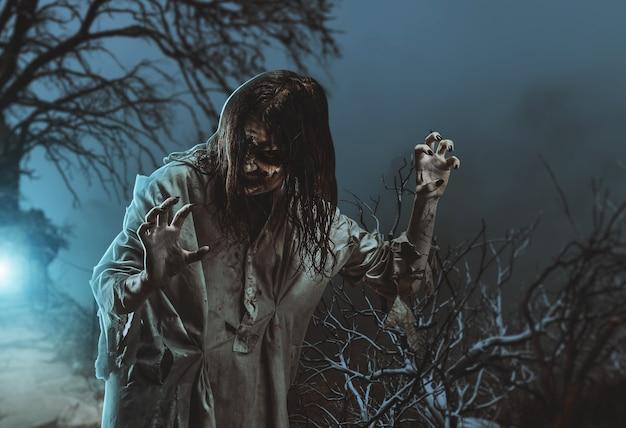 Zombie aterrador contra un árbol. víspera de todos los santos.