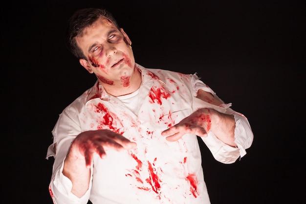 Zombie embrujado con sangre en su rostro sobre fondo negro.