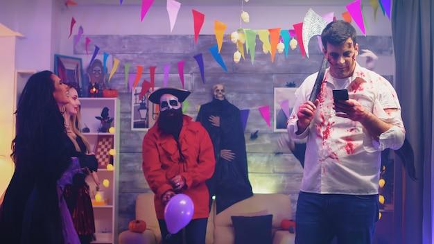 Zombie espeluznante con un hacha usando su teléfono en la fiesta de halloween con otras personas disfrazadas de monstruos.