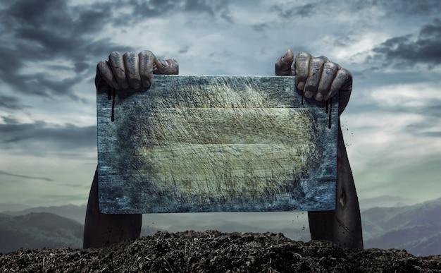 Zombie mano que sostiene la vieja tabla de madera